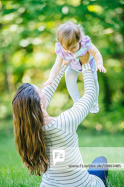 Woman lifting up toddler daughter in park
