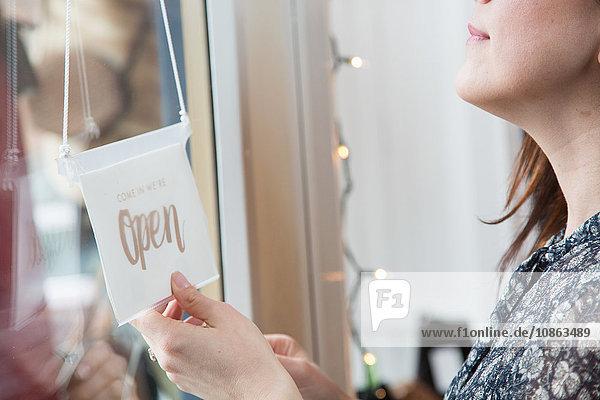 Geschäftsfrau dreht Beschilderung an der Tür in einem Oldtimerladen