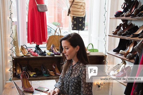 Geschäftsfrau arbeitet am Laptop im Vintage-Laden