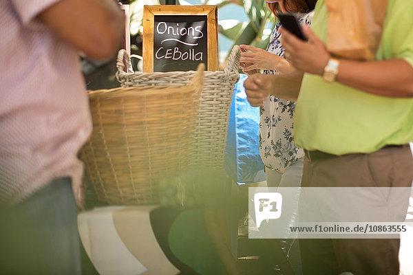 Menschen stehen um Zwiebelkörbe auf dem Markt