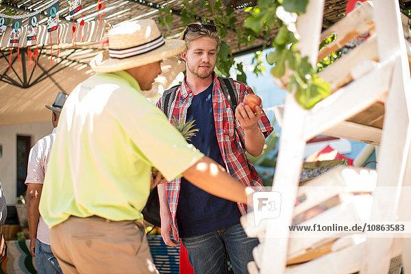 Tourist kauft Obst vom Markthändler