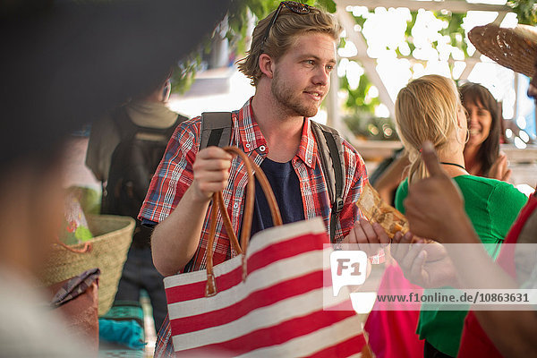 Tourist paying for tote bag to market trader