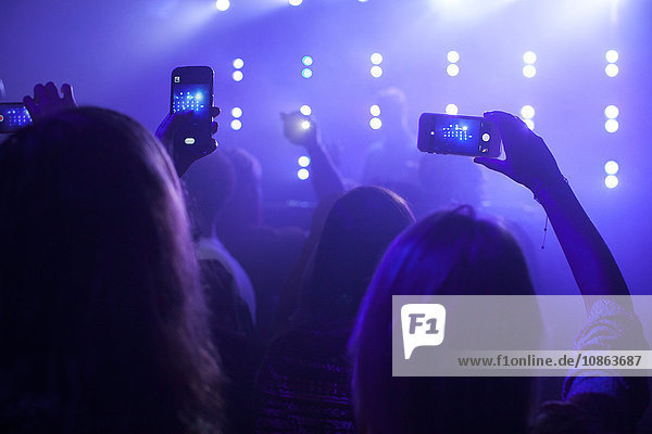 group of people at concert  taking photographs of stage  using smartphones  rear view