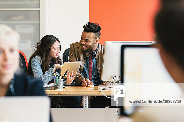 Kollegen im Büro schauen lächelnd auf das digitale Tablet