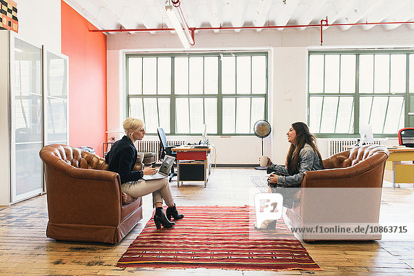 Colleagues in office sitting face to face on sofas