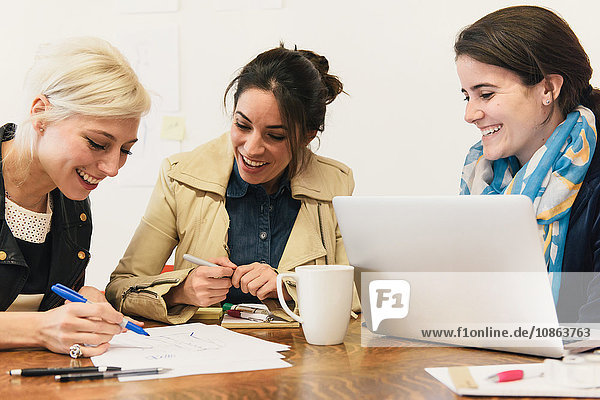 Women sitting at table with laptop making notes