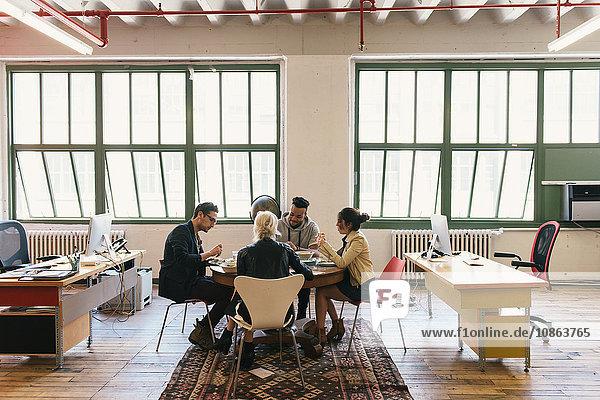 Kollegen am Tisch beim Mittagessen im Büro