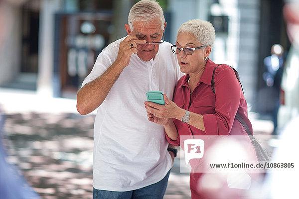 Älterer Mann und Frau lesen Smartphone in der Stadt