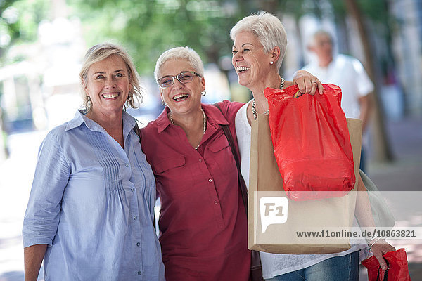 Portrait of senior and mature women with shopping bags in city