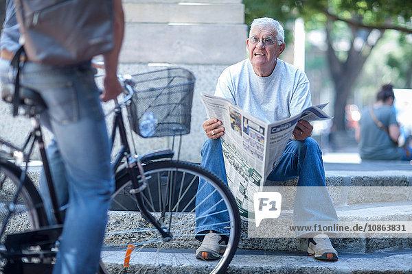Älterer Mann auf Stadttreppe im Gespräch mit Radfahrer