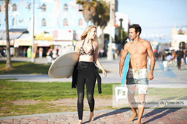 Surfing couple carrying surfboards at Venice Beach  California  USA