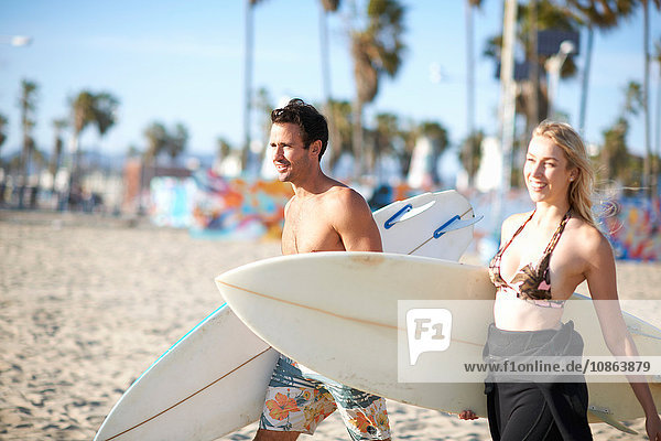 Surfing couple carrying surfboards on Venice Beach  California  USA
