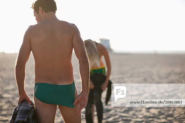 Rear view of surfing couple putting on wetsuits on Venice Beach  California  USA