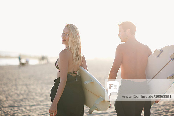 Surfing couple carrying surfboards on sunlit Venice Beach  California  USA