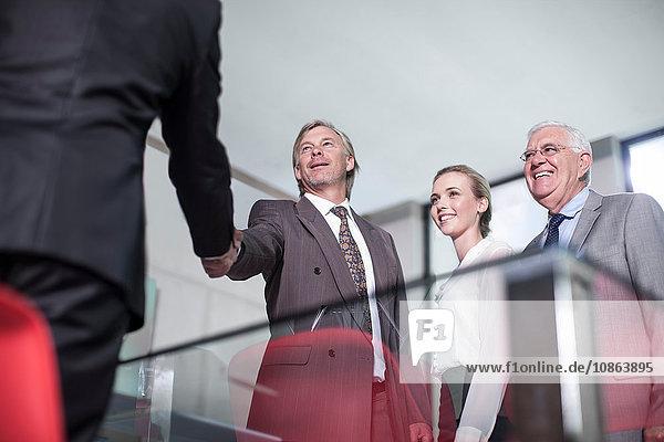 Geschäftsteam gibt sich bei Bürobesprechung die Hand