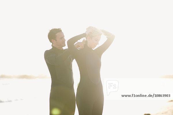 Surfer-Paar mit Neoprenanzügen am sonnenbeschienenen Venice Beach  Kalifornien  USA