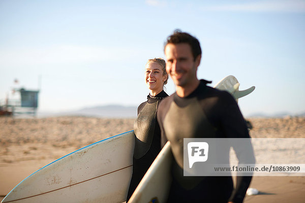 Surfing couple strolling with surfboards on Venice Beach  California  USA