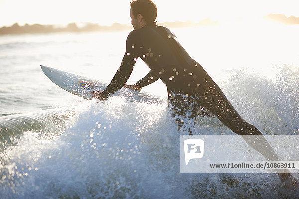 Männlicher Surfer surft in die Meereswelle am Venice Beach  Kalifornien  USA