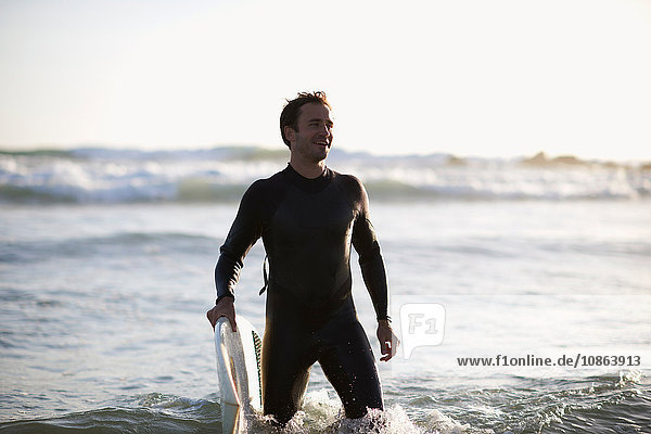 Male surfer standing in sea on Venice Beach  California  USA