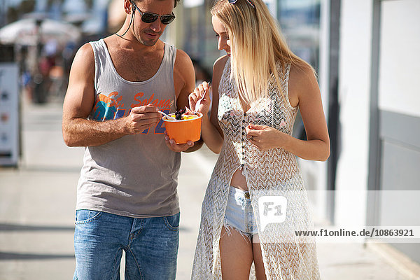 Couple strolling and eating frozen yoghurt on sidewalk  Venice Beach  California  USA