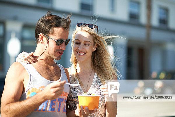 Spaziergang zu zweit und gemeinsame Nutzung von gefrorenem Joghurt auf dem Bürgersteig  Venice Beach  Kalifornien  USA
