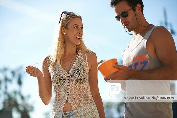 Paar beim Spaziergang und beim Verzehr von gefrorenem Joghurt am Venice Beach  Kalifornien  USA
