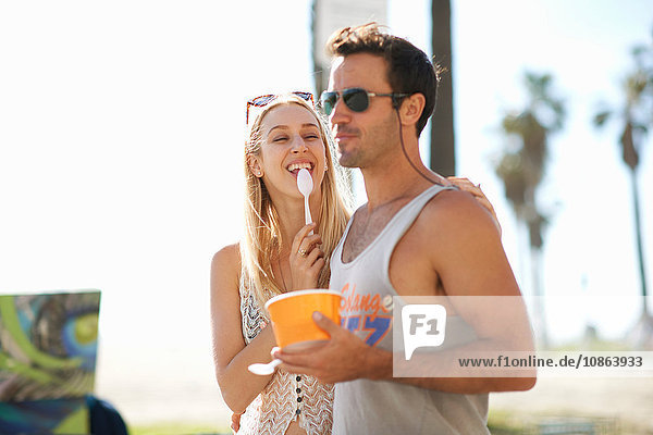 Couple strolling and eating frozen yoghurt at Venice Beach  California  USA