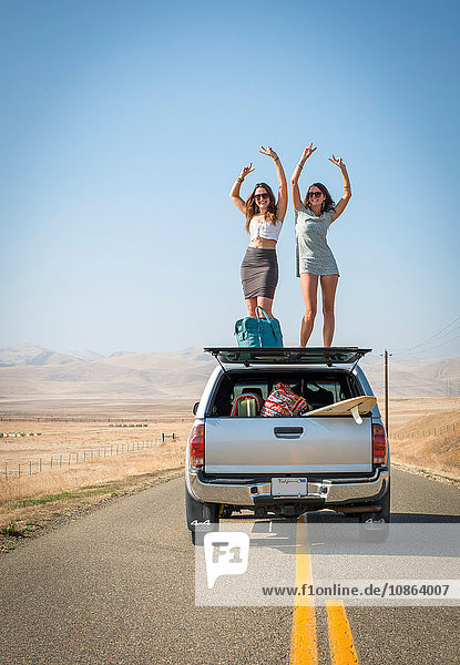 Women standing on car roof  Highway 1  California  USA