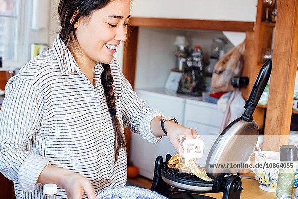 Frau in der Küche beim Entnehmen der Waffel aus dem Waffeleisen lächelnd