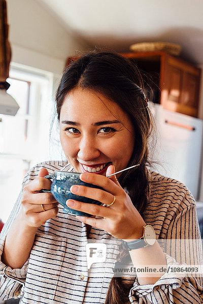 Frau hält Teetasse an den Mund und schaut lächelnd in die Kamera