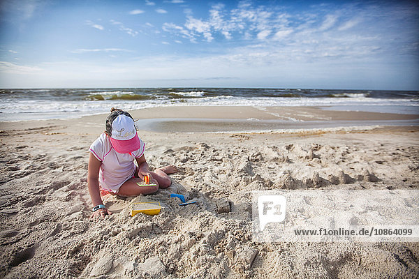 Girl sitting on beach playing in sand