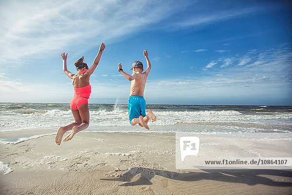 Rear view of girl and boy on beach arms raised jumping in mid air