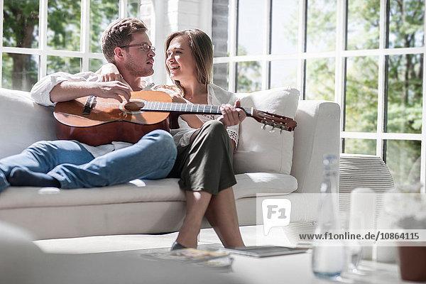 Gitarre spielendes Paar auf dem Sofa
