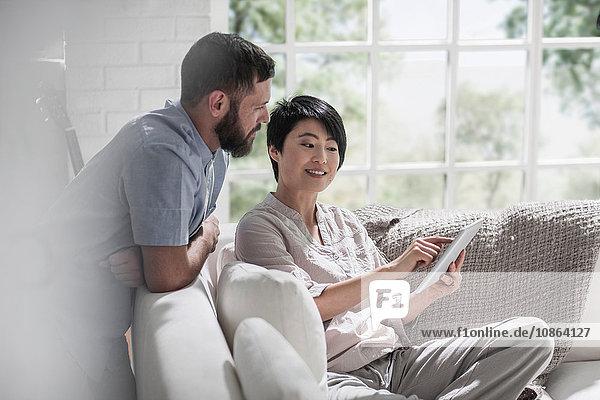 Ehepaar mit digitalem Tablett auf dem Sofa
