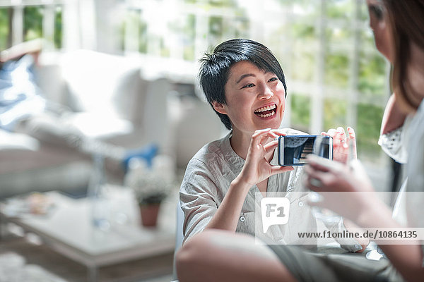 Frau zeigt einem Freund ein Foto im Smartphone