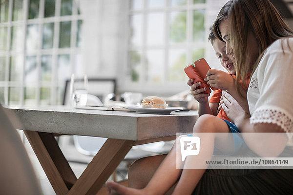 Mutter und Sohn benutzen Smartphone am Esstisch