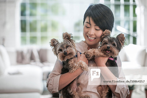 Glückliche Frau umarmt Haushunde zu Hause