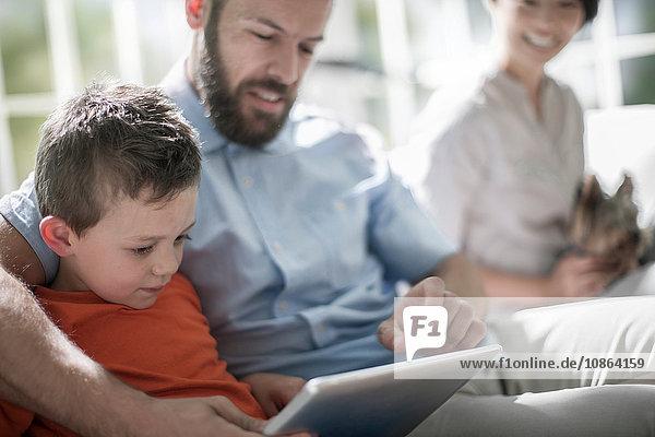 Vater und Sohn mit digitalem Tablett  Mutter mit Hund im Hintergrund
