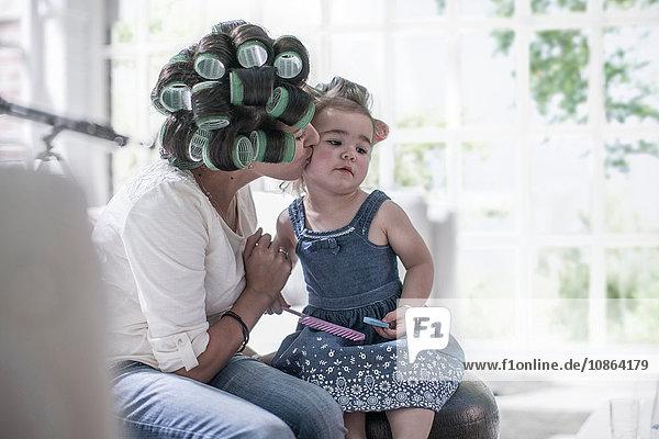 Mutter in Haarrollen küsst Tochter auf die Wange