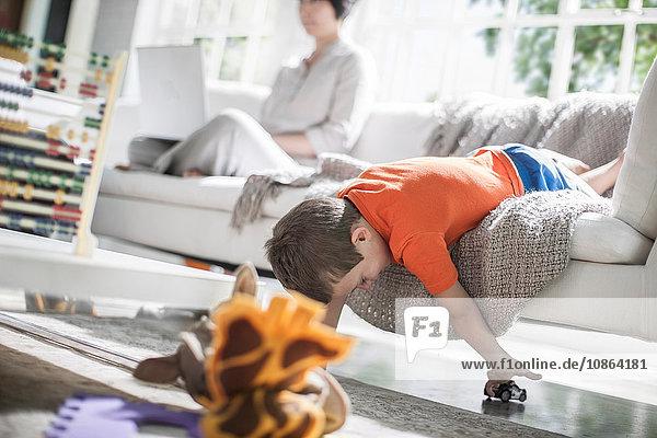 Junge spielt auf Sofa  Mutter im Hintergrund