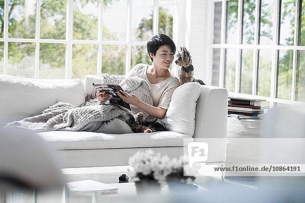 Frau liest auf Sofa mit Haushunden