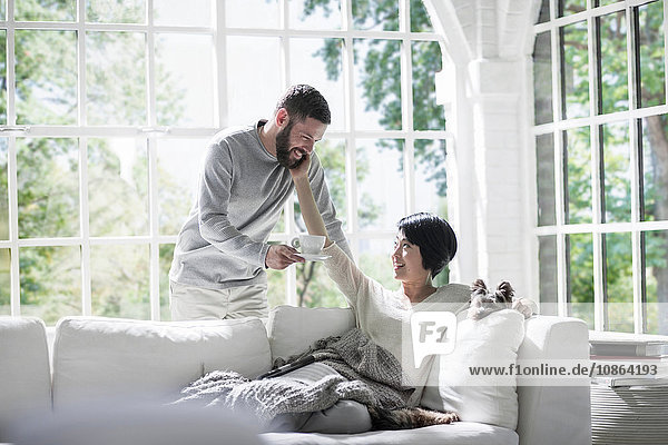Ehemann bringt der Frau Kaffee auf dem Sofa