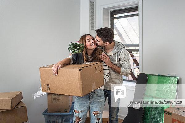 Umzug: junge Frau trägt einen Pappkarton  junger Mann küsst sie auf die Wange