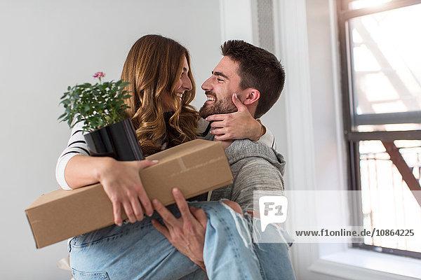 Umzug: Junger Mann trägt junge Frau in neues Zuhause Umzug: Junger Mann trägt junge Frau in neues Zuhause