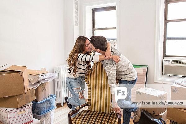 Umzug: Junges Paar umarmt sich über Stuhl