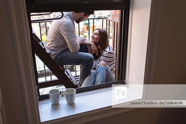 Junges Paar sitzt auf der Feuertreppe und lächelt