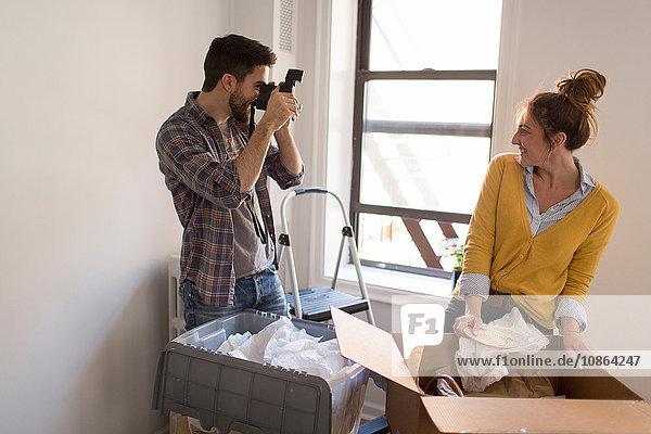 Umzug: Junges Paar packt aus  junger Mann fotografiert junge Frau