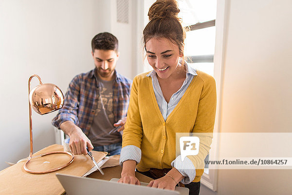 Moving house: Young man unpacking box  young woman using laptop