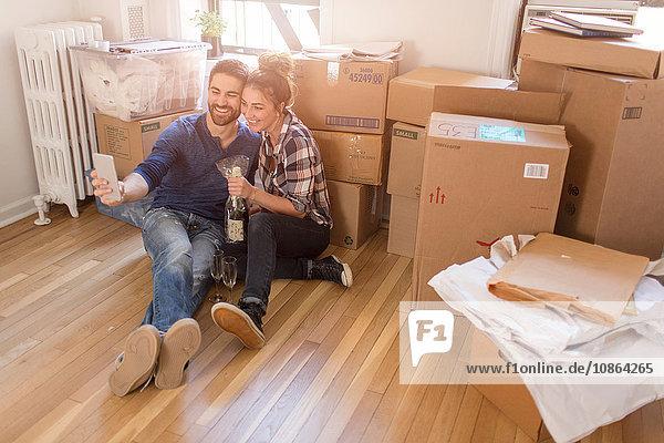 Umzug: Junges Paar sitzt in einem Zimmer voller Kisten  hält eine Champagnerflasche in der Hand und macht ein Selbstporträt mit einem Smartphone