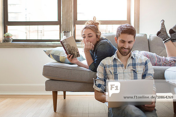 Young couple relaxing at home  young woman reading book  young man using laptop